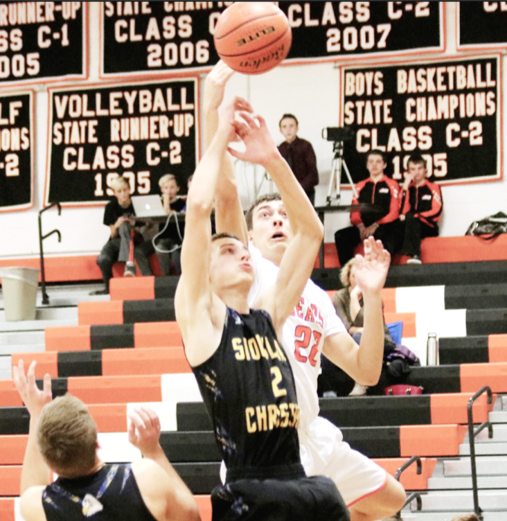 LCC's Noah Schutte goes over Christian Heilbuth of Siouxland Christian to snag the rebound during Thursday's season opener.